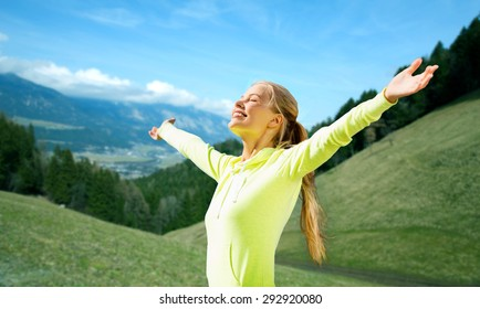 fitness, sport, people and emotions concept - happy woman in sportswear enjoying sun and freedom over mountains, green fields and blue sky background