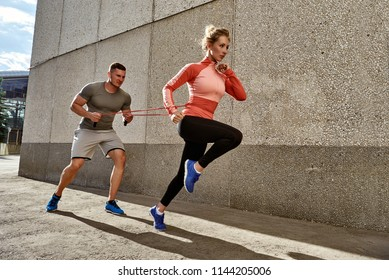 fitness, sport, people, exercising and lifestyle concept - couple running upstairs on city stairs.