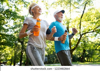 Fitness, sport, people, exercising and lifestyle concept - senior couple running