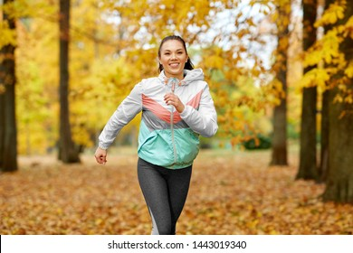 fitness, sport, people and healthy lifestyle concept - young woman running in autumn park