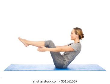 fitness, sport, people and healthy lifestyle concept - woman making yoga in half-boat pose on mat