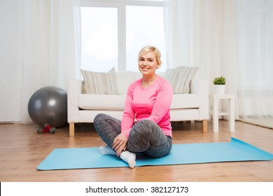 fitness, sport, people and healthy lifestyle concept - happy plus size woman sitting on mat at home