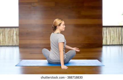 fitness, sport, people and healthy lifestyle concept - woman making yoga in twist pose on mat over wooden gym background