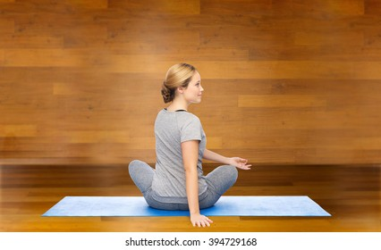 fitness, sport, people and healthy lifestyle concept - woman making yoga in twist pose on mat over wooden room background