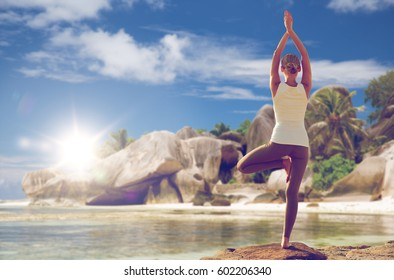 fitness, sport, people and healthy lifestyle concept - woman meditating in yoga tree pose over exotic beach background from back