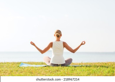 fitness, sport, people and lifestyle concept - of woman making yoga exercises on mat outdoors from back