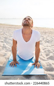fitness, sport, people and lifestyle concept - man doing yoga exercises lying on mat outdoors