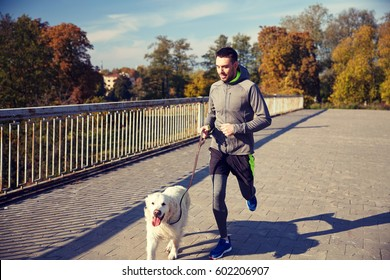 fitness, sport, people, pets and jogging concept - happy man with labrador retriever dog running outdoors