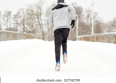 fitness, sport, people, season and healthy lifestyle concept - young man running along snow covered winter bridge road