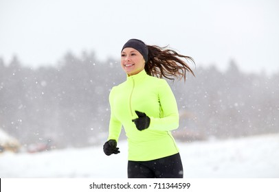 fitness, sport, people, season and healthy lifestyle concept - happy woman running along snow covered winter road