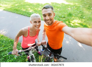 fitness, sport, people, technology and healthy lifestyle concept - happy couple with bicycle taking selfie outdoors