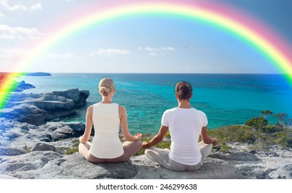 fitness, sport, people, yoga and lifestyle concept - happy couple meditating in lotus pose on summer beach from back