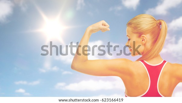 fitness, sport, power, strength and people concept - happy sporty young woman showing biceps over sky and sun background
