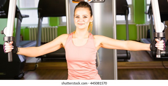 fitness, sport, power-lifting and people concept - sporty girl building some muscles on a simulator