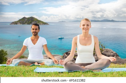fitness, sport, recreation and people concept - happy couple making yoga exercises sitting on mats outdoors over ocean background