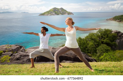 fitness, sport and relax concept - couple making yoga in warrior pose over natural background