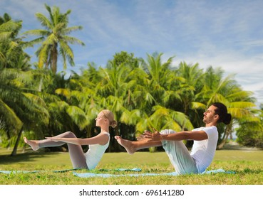 fitness, sport, relax and people concept - couple making yoga half-boat pose over exotic natural background with palm trees