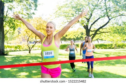 fitness, sport and success concept - happy woman winning race and coming first to finish red ribbon over group of sportsmen running marathon with badge numbers at park