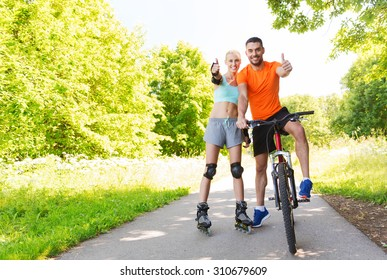 fitness, sport, summer, people and healthy lifestyle concept - happy couple with roller skates and bicycle showing thumbs up outdoors at park
