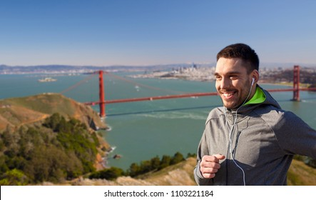 fitness, sport and technology concept - happy man running and listening to music in earphones over golden gate bridge in san francisco bay background