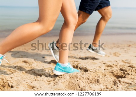 ee08ef779 fitness, sport and technology concept - legs of couple of sportsmen in  sneakers running along