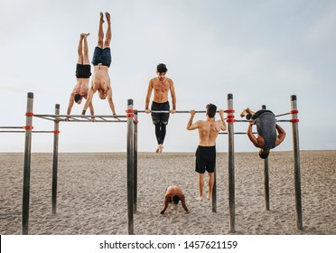 fitness, sport, training, calisthenics and lifestyle concept - Group of guys training on the beach workout bars