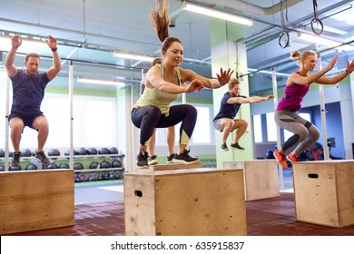 fitness, sport, training and exercising concept - group of people doing box jumps in gym