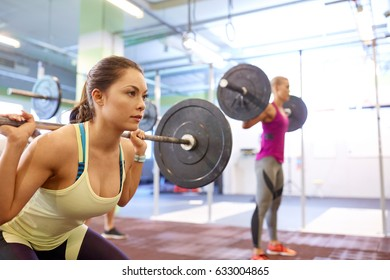 fitness, sport, training, exercising and lifestyle concept - group of people with barbells doing squats in gym