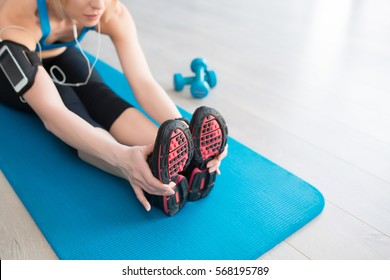 Fitness, sport, training at the gym, healthy lifestyle concept. Young woman stretching near big windows with earphones at home