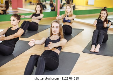 Fitness, sport, training, gym and lifestyle concept - group of smiling women exercising on mats in the gym.