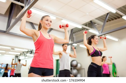 fitness, sport, training, gym and lifestyle concept - group of smiling people working out with dumbbells in the gym