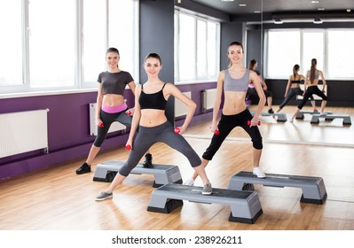 Fitness, sport, training, gym and lifestyle concept. Three young women are working out with steppers in gym.