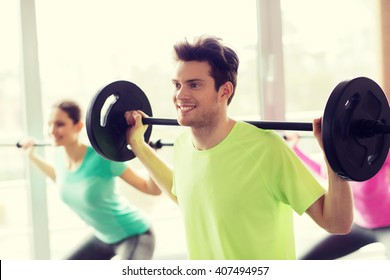 fitness, sport, training, gym and lifestyle concept - group of people exercising with barbell in gym