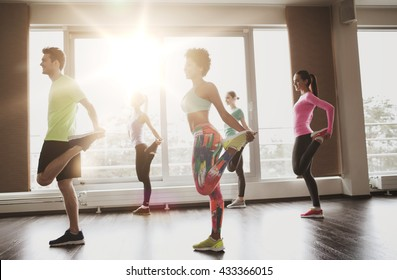 fitness, sport, training, gym and lifestyle concept - group of smiling people with trainer exercising and stretching in gym