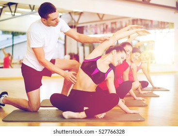 fitness, sport, training, gym and lifestyle concept - group of smiling women with male trainer stretching on mats in the gym