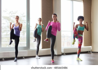 fitness, sport, training, gym and martial arts concept - group of women working out and fighting in gym