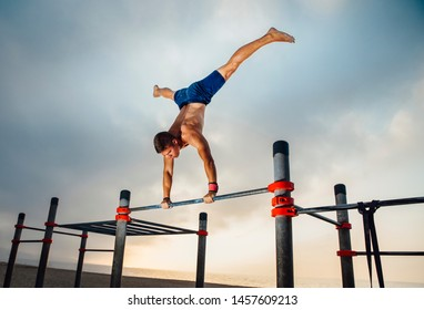 fitness, sport, training and lifestyle concept - young man exercising handstand on bar outdoors - calisthenics