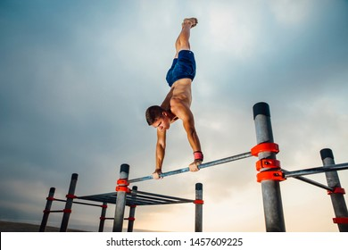 fitness, sport, training and lifestyle concept - young man exercising olympic handstand on bar outdoors - calisthenics