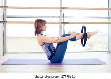 fitness, sport, training and lifestyle concept -  girl doing pilates with ring