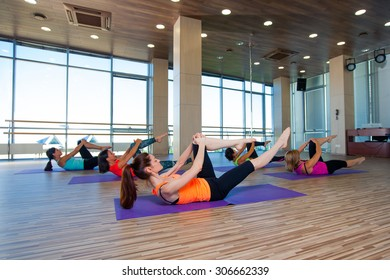 fitness, sport, training and lifestyle concept - group of smiling women stretching in gym.