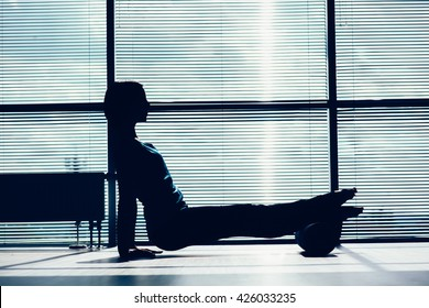 fitness, sport, training and lifestyle concept - woman doing pilates on the floor with foam roller contour of the body against the window