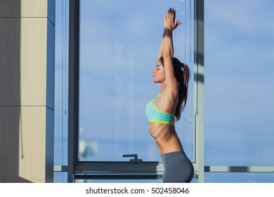 fitness, sport, training and lifestyle concept - smiling woman stretching on mat in gym. light from a large window.