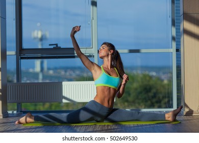 fitness, sport, training and lifestyle concept - smiling woman stretching on mat in gym. light from a large window. selfie