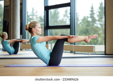 fitness, sport, training and people concept - smiling woman doing abdominal exercises on mat in gym