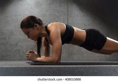 fitness, sport, training and people concept - woman doing plank exercise on mat in gym