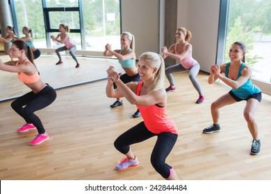 fitness, sport, training, people and lifestyle concept - group of women making squats in gym