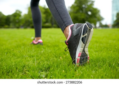 fitness, sport, training, people and lifestyle concept - close up of exercising woman legs on grass in park