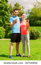 fitness, sport, training, technology and lifestyle concept - two smiling people with smartphones and earphones outdoors