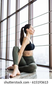 fitness, sport, training and yoga concept - smiling woman stretching leg in gym