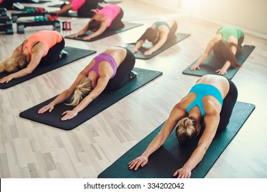fitness, sport, training, yoga and people concept - smiling woman doing exercise in gym
